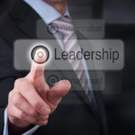 A businessman Pointing to a leadership button on a clear screen.